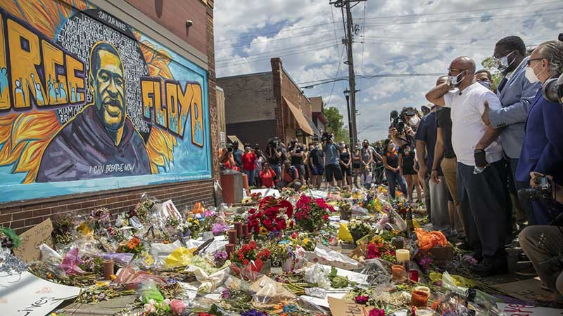 George Floyd memorial mural painted on wall of cup foods where Floyd was arrested. Mourners gather in a circle. The ground is covered with notes, candles, and flowers.