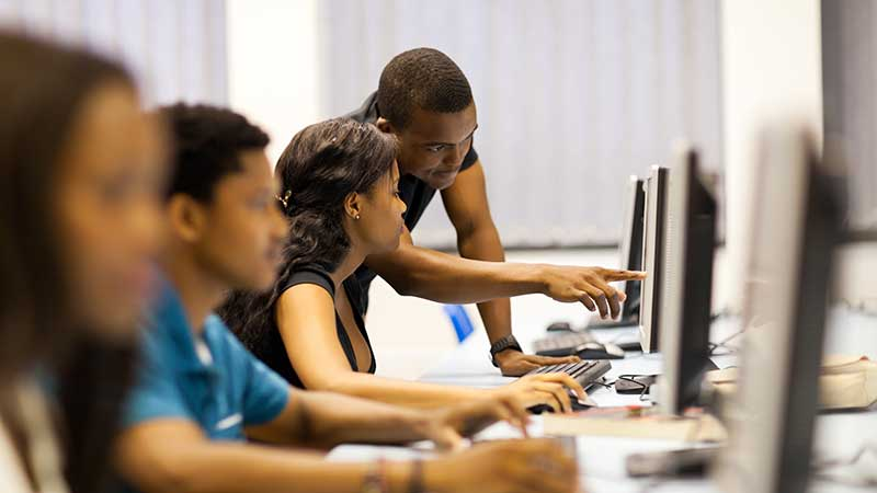 Black students working together at computer. Stock art.