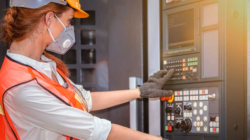 Factory worker with braided red hair in orange safety suit, hardhat, COVID mask and glove operates a complex control panel with dozens of dials and buttons and a built-in flat panel screen.