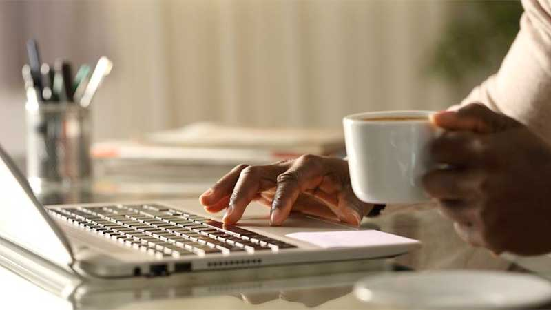 Stock photo of a Black man's hand on a laptop, the other hand holding a coffee cup.