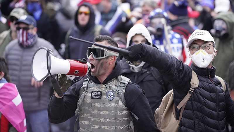 Rioter in crowd shouting into a megaphone.
