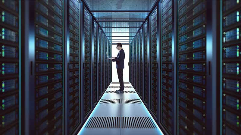 Dark silhouette of man down a dark corridor in a glowing server farm.