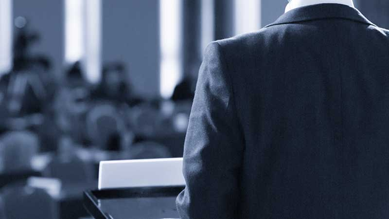 Faceless dude in a suit coat pictured from the back standing at a lectern addressing a blurry crowd of people.