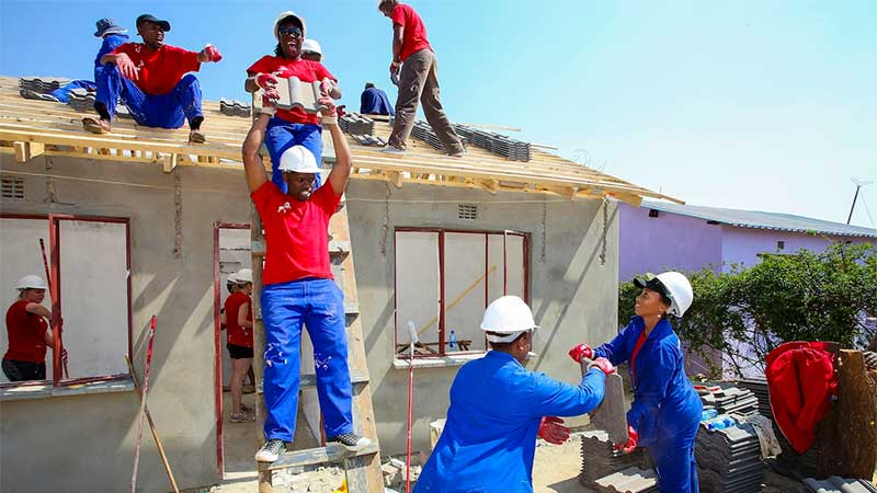 A team of volunteers builds a house.