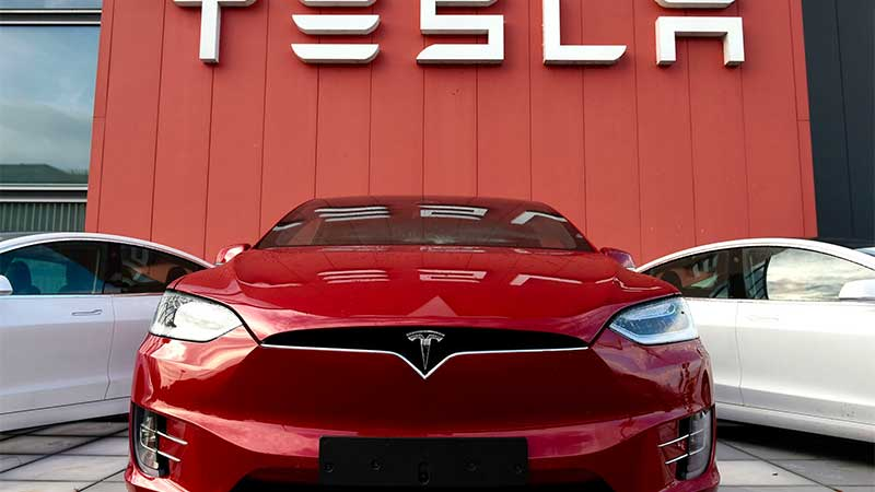 Red Tesla with Tesla sign in the backgroun.