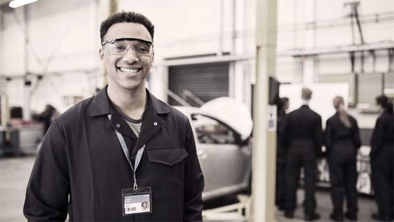 Young, Black worker, smiling, wearing safety glasses and a lanyard.