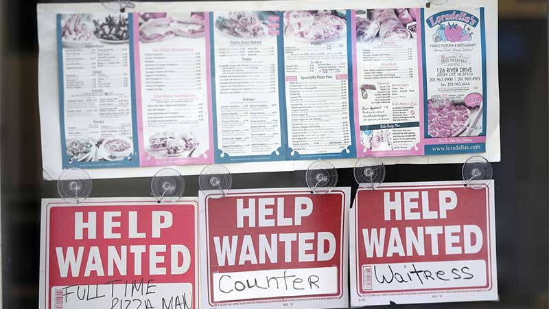 Three help wanted signs in a restaurant window, one for Waitress, Counter, and Full-Time Pizza Man.